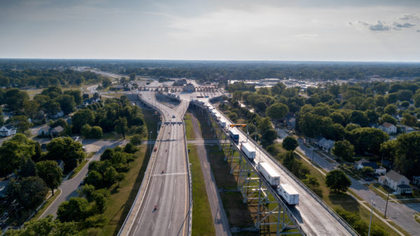 An Aerial View Of A Line Of Semi Trucks Waiting At The Canadian Border To Enter The USA